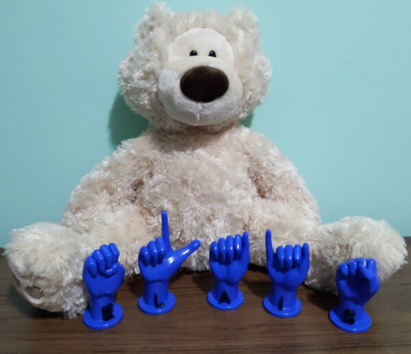 """Letters """"ELIAS"""" in blue with black letters in front of a stuffed bear"""