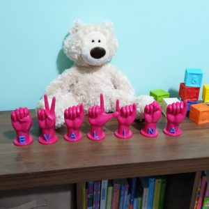 """Letters """"EVALINA"""" in magenta with glow in the dark blue letters in front of a stuffed bear"""